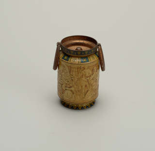 Oval tin with ring handles and decoration resembling an Egyptian frieze.
