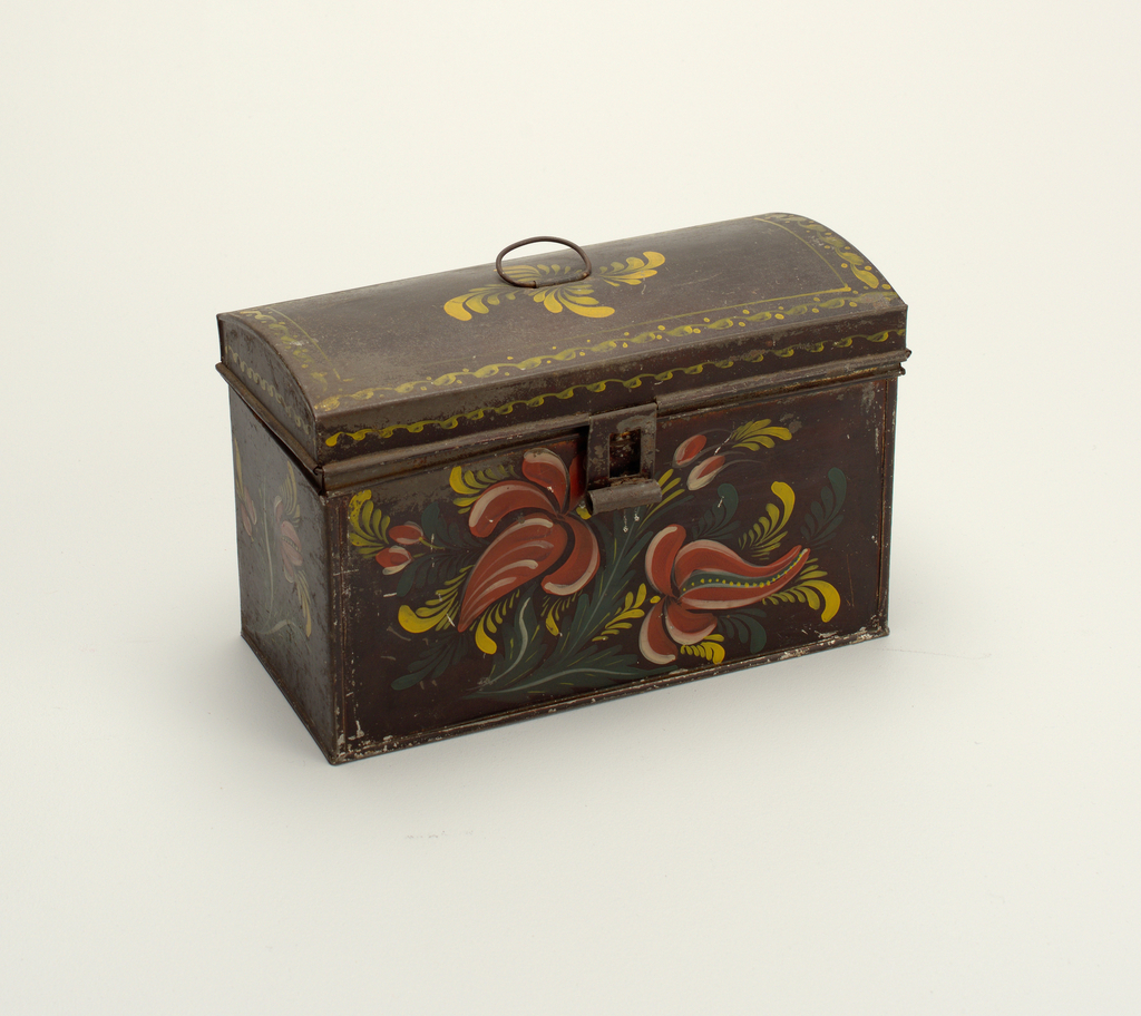 """Rectangular box with hinged cover domed from front to back. Ring bail handle on top of cover and hasp fastener, with staple broken off.  Box is painted black with floral decoration on front and ends of vermillion fruit-like flowers, with white and alizarin markings, and with serrated green leaves and leaf-fronds. Cover is decorated on front and ends with a border of lapped and recumbent """"S""""s in yellow and similar band with dots frames the top. Spiral arrangement of leaf-fronds in yellow around handle."""