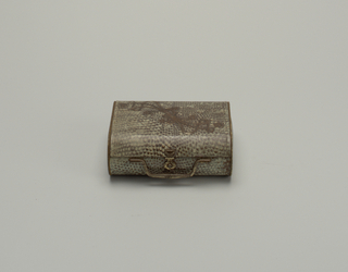 In the form of a purse handbag made of shark or reptile skin. The lid has an embossed ribbon-like design running diagonally across it. Gold-tone clasp and handle.