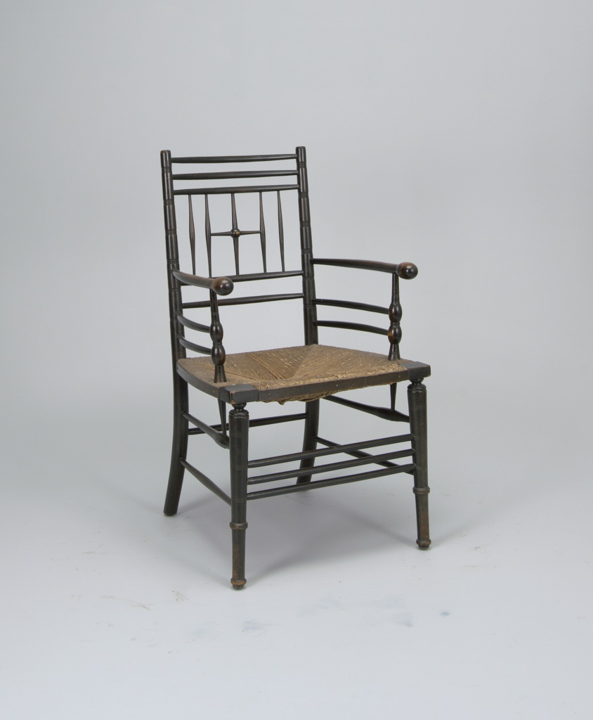 Ebonized beech armchair with turned back sections, supports, and legs.  Rush seat set into frame.
