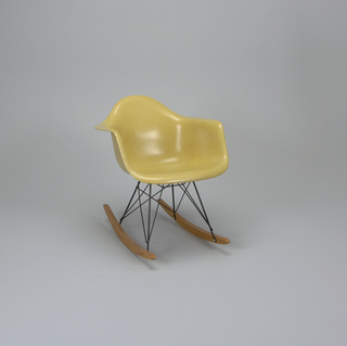 Light yellow bucket seat surmounting criss-crossed metal rod legs on curved wooden rockers.