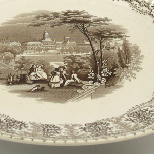 Brown decoration over white. There is a floral border around rim. Central design shows figures in a park overlooking City Hall.