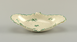 Oval dish wish scalloped border in the form of a shell. A line of green and traced of gilding at border. Center shows scattered sea flora in green and black.