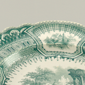 Scalloped-edge plate with green transfer-printed decoration on white ground. Central scene depicting Renaissance couple surrounded by classical architectural structures, columns, urns and mountainous landscape. Border of four alternating cartouches, two with architectural motifs, two with baskets of blooming flowers; between each reserve are dense patterns with alternating decorative motifs.