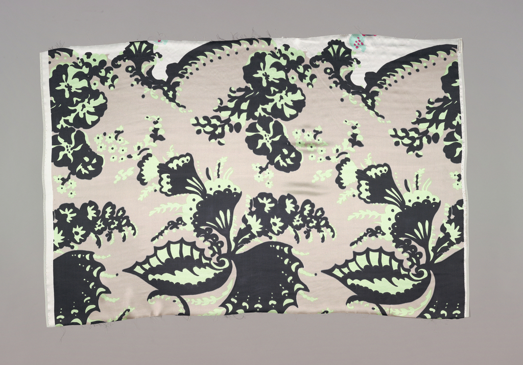 "Printed in flesh color, green and black.  Pattern shows large scale swirling ""bizarre"" design of wings and floral elements."