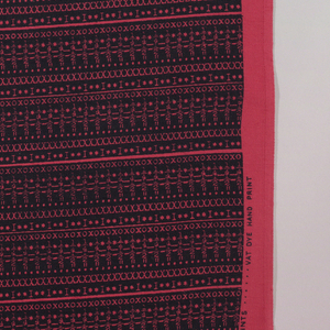Length of printed cotton with horizontal stripes made by repetition of typewriter keys. Dyed bright red-pink and overprinted with black.