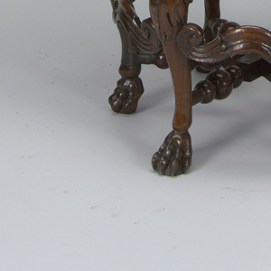 Circular caned seat on six cabriole legs with leaf-carving and paw feet joined by turned stretcher; the curved back with turned uprights, carved scrollwork and three medalions pierced and carved with foliage.