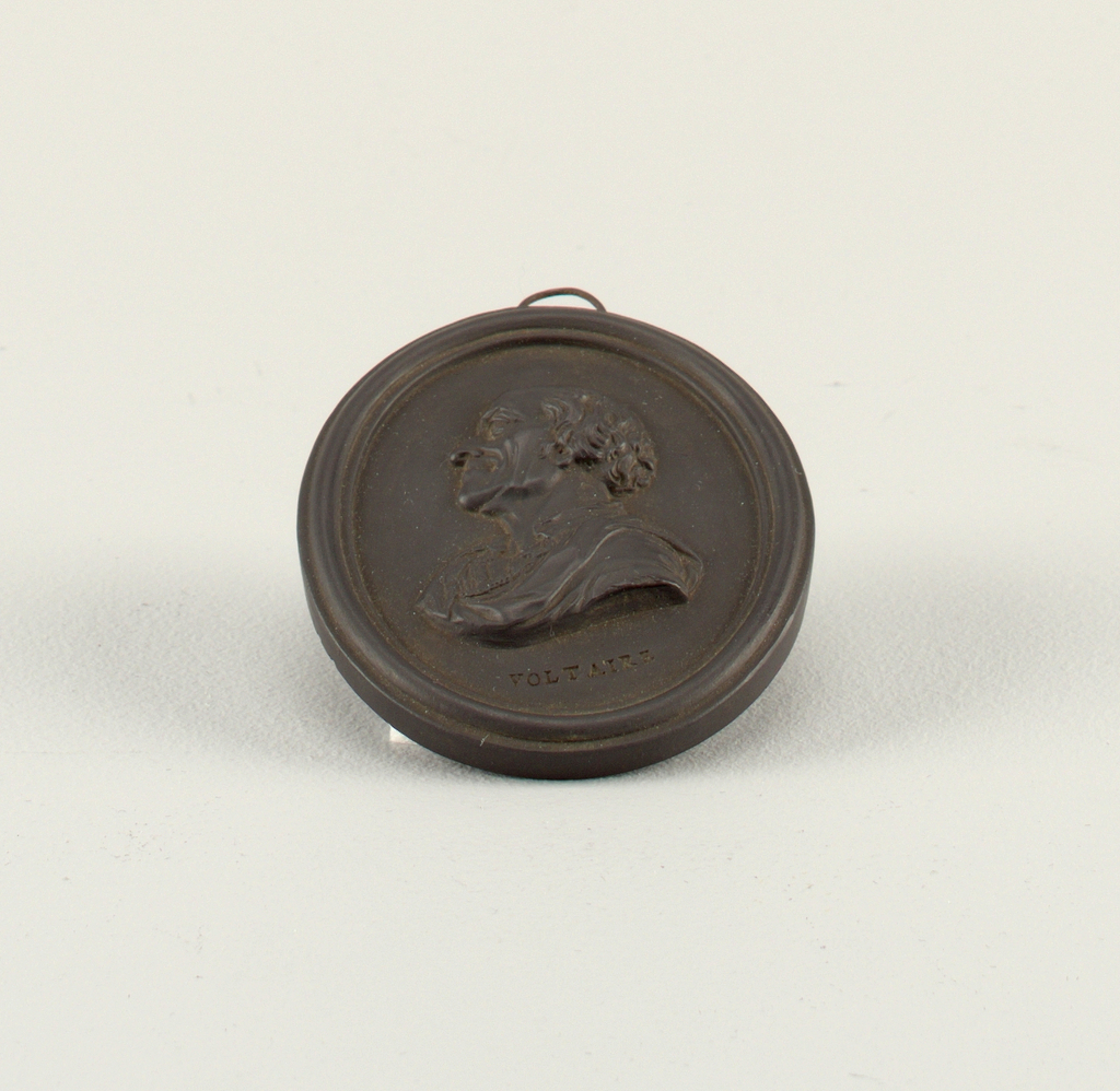 Oval, with molded border. Head and shoulder portrait, in profile to left, showing François-Marie Arouet, Voltaire (1694–1778). Slot at top for suspension.