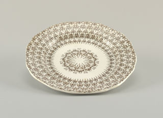 Plate with brown transfer-printed decoration on white ground in a triangular, geometric pattern.