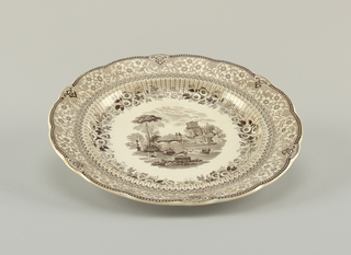Plate has a scalloped edge.There is a floral pattern around the rim with a central scene showing boats on a river and architectural monuments. Brown decoration over white.