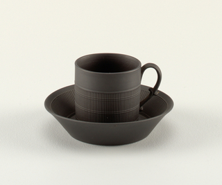 Cylindrical cup with scrolling handle, body decorated with molded reeding on the lower two-thirds. Flat saucer with flaring edge, interior molded with reeding. Matt black.