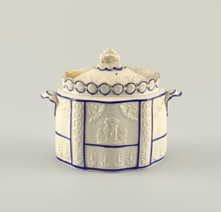 Bowl molded with relief decoration showing palmettes and a woman standing before a classical bust. Raised guilloche crown and handles. Lid with floral finial.