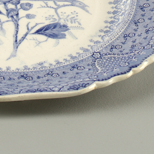 Scalloped-edge plate with blue transfer-printed decoration on white ground. Central image of branches with blossoming flowers and foliage. Border with dense flower motifs, flower swags and other decorative patterns.