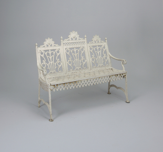 Iron bench for three people painted white. Scalloped apron. Scrolling and crowned backrest.  In iron at center: M.L. Abrams