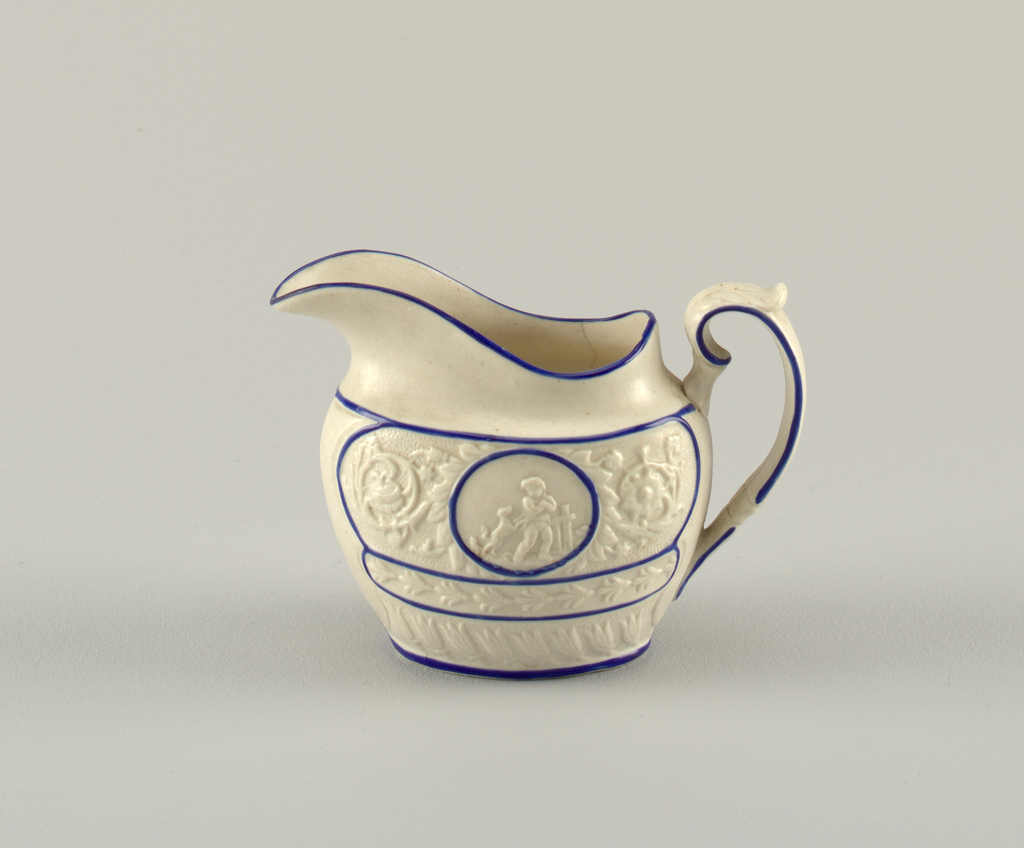 Bowl pitcher with floral relief decoration and a medallion of a boy with dog. Outlines in blue.