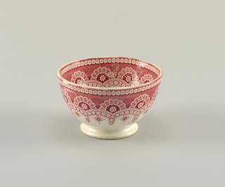 Red-printed, footed bowl with a repeat scalloped pattern resembling lacework on exterior and interior, central rosette motif printed on bottom interior.