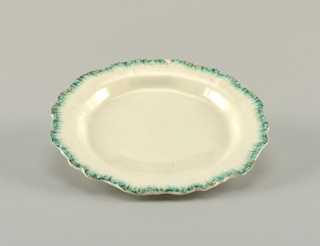 Round plate with scalloped border resembling a shell. Edge with painted green lines and traces of gilding.
