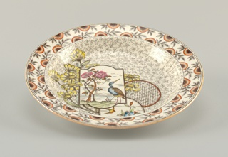 Circular form with slightly concave rim, the white crackled ground with Japanese-inspired transfer printed polychrome decoration: stylized flowers and leaves on rim, the well with a panel and two medallions respectively, showing a crane(?) in landscape, a bird in flight over flowering branch, and a geometric pattern; all superimposed on a sprig of naturalistically rendered yellow flowers on a field of small leafy stems.