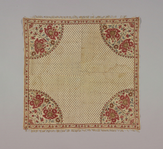 Small square table cover, pieced, of cream-color cotton block-printed in reds, violet, and green.  Corner design of large flowers and foliage; small all-over pattern of little buds.  Narrow floral border.  Green is blue over yellow.