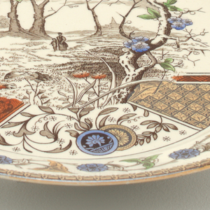 Circular form, the white ground with Japanese-inspired transfer printed polychrome decoration of a woman and child walking in a wooded landscape, the scene superimposed above bands and panels of geometric patterns and stylized flowers; the rim decorated with a geometric-patterned band encircling a ring of stylized flowers and leaves.