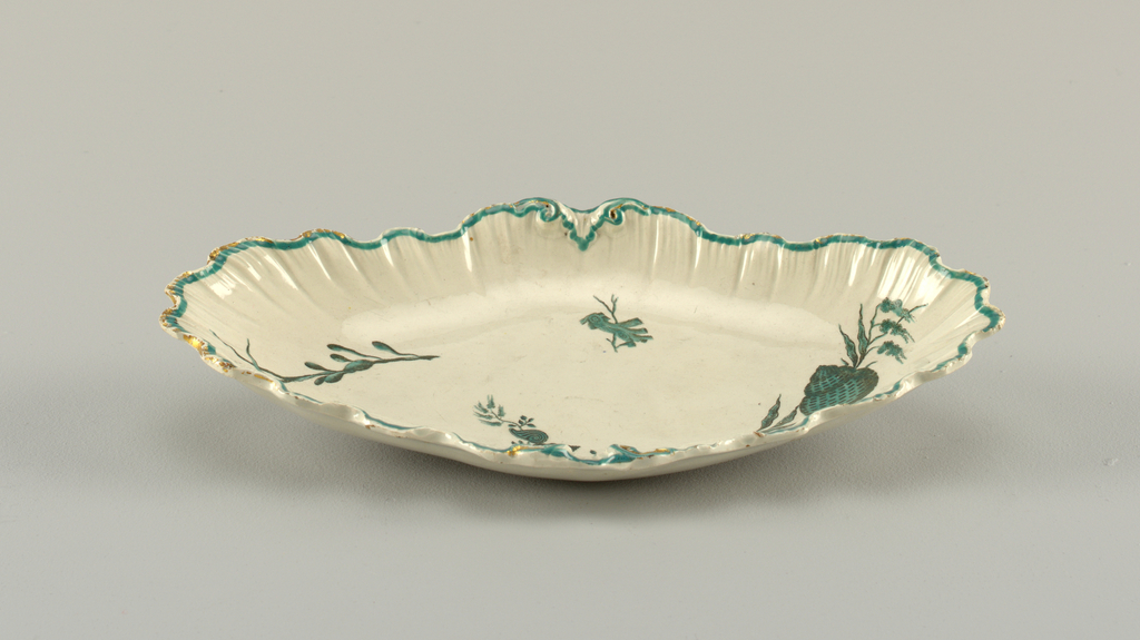 Oval dish with scalloped rim in the form of a shell. Green enamel line and traces of gilding at edge. At center, shells and sea plants in green and black.