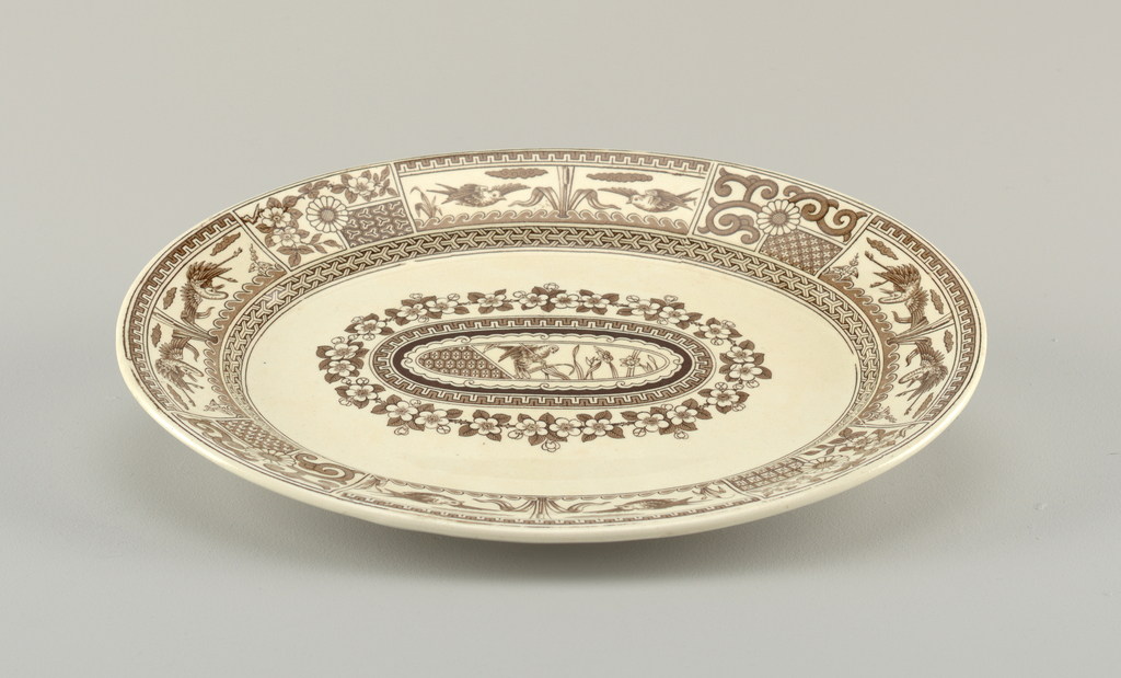 Of oval form, the cream colored crackled ground with Japanese-inspired brown transfer-printed decoration, the wide rim with panels ornamented with birds, flowers and geometric patterns; in center of platter is an oval band of flower blossoms surrounding an oval panel with geometric design on left, and scene of bird among flowering plants on right.
