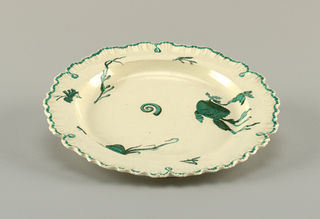 Round plate with scalloped edges that resemble a shell. Green line and traces of gilding at border.  Center shows shells and water flora in green and black.