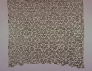 Sheer dress fabric with continuous repeat of traditional symmetrical stylized flowering pomeranate in grey on lighter grey ground.