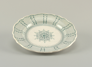 Scalloped-edge plate with green transfer-printed decoration on white ground. Large central flower decorative motif printed on center of plate. Border reveals alternating wide bands filled with rows of wavy, dotted lines; between each band are columns of interlocking flowers.