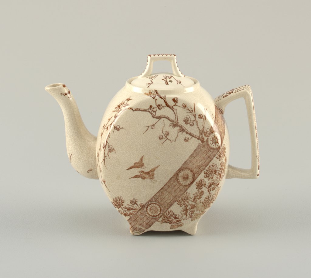 Teapot (a) of footed ovoid form with curving spout and squared handle, the crackled cream-colored ground with brown transfer-printed decoration of birds in flight among a tree and flowers, above a geometric-patterned band and a section with flower decoration. Sprays of flowering branches on spout, geometric pattern on handle.  The circular lid (b) decorated with sprays of flowering branches and geometric pattern on squared handle.