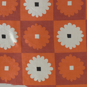 Abstracted chrysanthemum with a square in the center, on a checkboard of squares. Alternating color schemes: white flower with a black center on an orange ground, or an orange flower with a white center on a red ground.