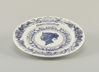 "Circular form, white ground with blue transfer-printed decoration: rim printed with a circle of flowers, thistles and flowing ribbons, and the words ""JUBILEE YEAR""; within rim ""COMPLIMENTS OF A. STOWELL & C"" printed above and below a wreath of laurel(?) leaves and a ribbon bearing the phrase ""VICTORIA DEI GRATIA REG. et IMP. 1837. 1887""; in center is a portrait bust of QueenVictoria in profile."