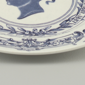 """Circular form, white ground with blue transfer-printed decoration: rim printed with a circle of flowers, thistles and flowing ribbons, and the words """"JUBILEE YEAR""""; within rim """"COMPLIMENTS OF A. STOWELL & C"""" printed above and below a wreath of laurel(?) leaves and a ribbon bearing the phrase """"VICTORIA DEI GRATIA REG. et IMP. 1837. 1887""""; in center is a portrait bust of QueenVictoria in profile."""