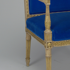 Rectangular backed blue velvet armchair with gold-colored trim.  Headpiece, seat frame, armrests, arm supports and legs in gilded wood.