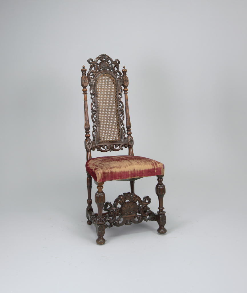 Tall back with turned posts, fluted and reeded on front surface, which rise to turned finials.  Caned central panel framed by a system of pierced scrolls and foliations.  Elaborate shell and scroll-carved pierced cresting and front stretcher which lies behind turned, gadroon-capped front legs.  Turned side and rear stretchers and rear legs.  Upholstered in red silk velvet with red silk fringe.