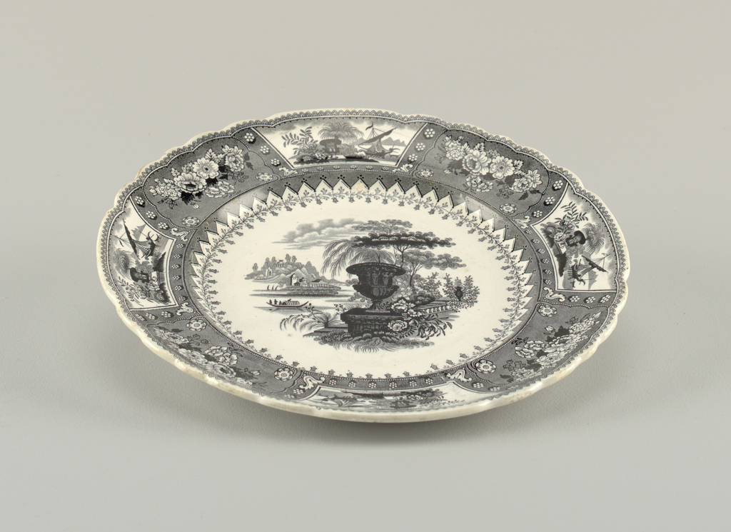 Black design over a white background. The plate has a slightly scalloped edge. There are four scenes around the rim alternating with floral arrangements. In the center is an outdoor scene with a large urn overlooking a river.