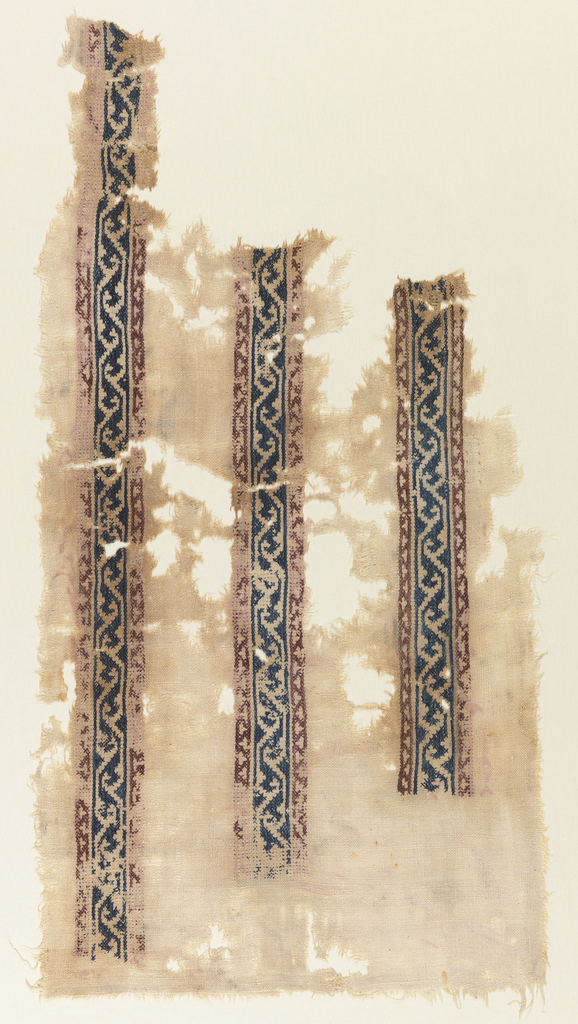 Section of undyed linen cloth with three parallel bands extending partially across it with interlocked continuous reserved scrolls on dark blue silk cross-stitch ground, red cross-stitch guard bands with small trefoil reserves.