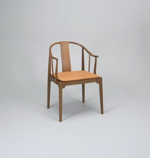 U-shaped top rail curving forward to produce the chair's arms.  Top rail carried by a wide splat, arm extensions each supported by three uprights, one of which is an upward extension of the back leg.  The cushion in natural leather on the seat is supported by bands of woven material, fitted into a wooden frame.  The seat is fitted on all four sides with a shaped, indented apron.