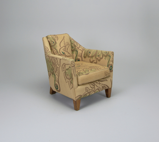 Angular, wing-armed chair, arms splayed outwards, deep rhomboid seat; upholsted in tan fabric with brown and green printed motif of birds fluttering or perched among leafy branches; four tapered wooden block feet.