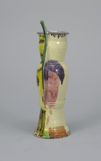 Tall pitcher painted with tan, dark green, purple, and red splotches. Applied elongated handle attached along body with projection at the top.