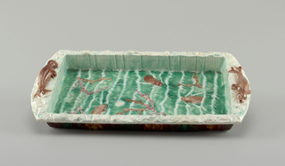 Molded rectangular tray. Straight sides, angled lip, extended at ends to form handles. Reclining seals molded on handles. Interior glazed with three swimming brown animals surrounded by green waves.