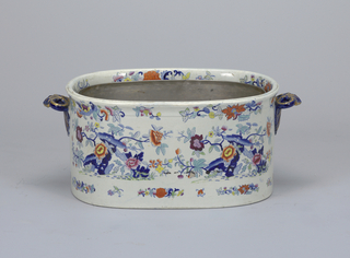 Deep oval vessel with Imari-style polychrome floral decoration. Scrolling gilt handles and metal insert.