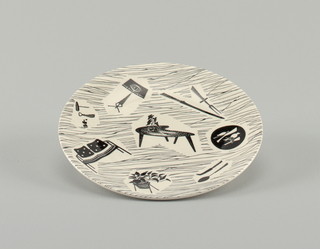 Circular molded plate with curved upturned edge; white ground printed with black irregular lines and twelve reserve vignettes with furniture, kitchen tools, plants, etc.