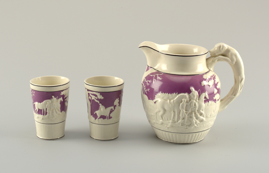 Round-bodied jug (a) with flaring lip. Body ornamented in relief with hunters in landscape, figures and trees white against plum background. Applied handle in form of dog. (b,c) Tumblers taper lip to base, with decoration matching that of jug.