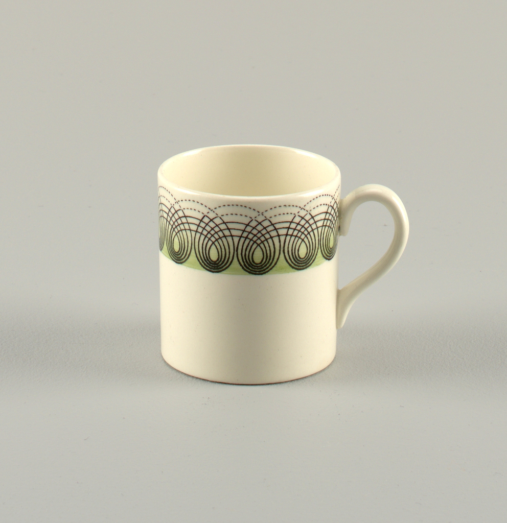 White porcelain cup and saucer decorated borders with concentric black loops all around border on light green ground.