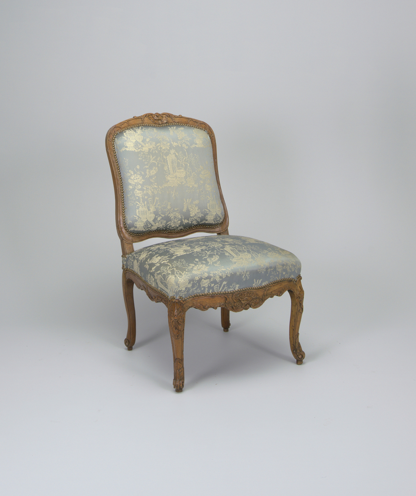 Pair of chairs, each with natural wood frame carved with foliage and rocaille motifs at crest rail, seat rail and knees; square seat on four cabriole legs terminating in feet on pegs; each back and seat upholstered in blue silk edged with brass studs.