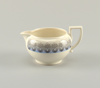 White porcelain pitcher with round body and curved handle flat at top; body decorated with concentric black loops all around border on light blue ground.