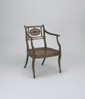 Chair has crozier posts and a narrow top rail.  Lower back rail is pierced with full and half lozenges.  A caned oval panel and two vertical splints included.  Simple curved arms are supported on stumps which curve out to meet extensions of curved, tapered, octagonal front legs.  Rear legs raked sharply backwards.  Caned seat.  On black ground, gilded design of panels and lines.
