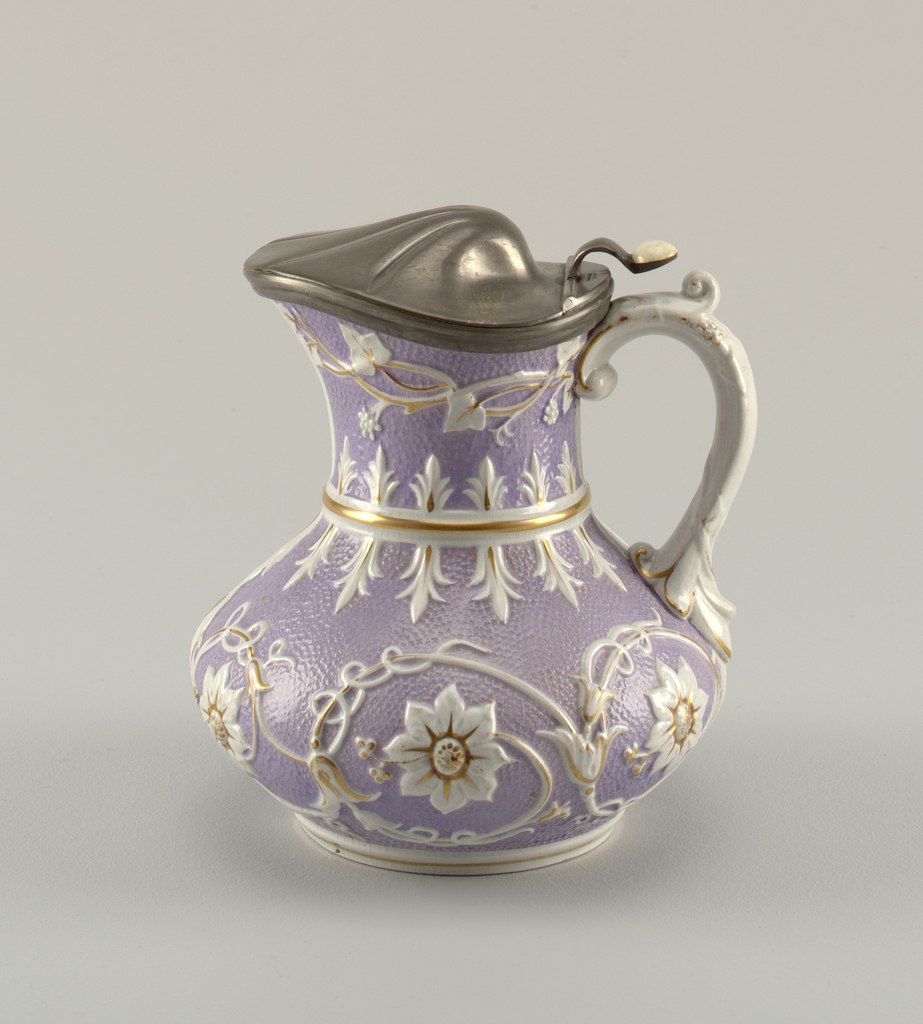 """Body of squat pear shape, on circular molded base. Molded band between body and flare neck. Applied scrolled handle. Body with """"orange skin"""" texture overall, glazed in mauve. Raised decoration in white of floral rosettes and tendril vines; decoration highlighted with gilding. Jug fitted with hinged metal cover in the form of a domed shell. Thumbpiece above scroll handle fitted with ceramic button."""