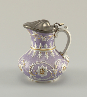 "Body of squat pear shape, on circular molded base. Molded band between body and flare neck. Applied scrolled handle. Body with ""orange skin"" texture overall, glazed in mauve. Raised decoration in white of floral rosettes and tendril vines; decoration highlighted with gilding. Jug fitted with hinged metal cover in the form of a domed shell. Thumbpiece above scroll handle fitted with ceramic button."